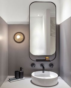 Mirror, sink, lighting. Looks like a grey surround has been applied to the lower part of the wall as a backsplash effect.