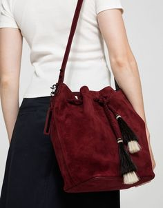 From Loeffler Randall, a minimalist shoulder bag in Port. Featuring a leather construction, main compartment with drawstring closure and horse hair tassels, adjustable strap, two interior pockets, interior zip pocket, detachable branded fob and structured