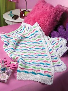 "Brighten a youngster's room with this easy ripple afghan highlighted with wavy stripes of fun colors. This e-pattern was originally published in the February 2012 issue of Crochet World magazine. Size: 36"" x 49"". Made with medium (worsted) weight yarn and size I/9/5.5mm hook.Skill Level: Easy"