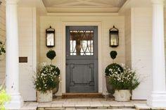 pretty entry. love the door, lanterns, flowers, columns, wood porch...ok, EVERYTHING! :)