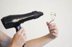 Secadora de cabello soplando sobre un rizador de pestañas
