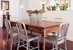Tacos de madeira e mesa mineira em pinho-de-riga conferem rusticidade à sala de jantar da decoradora Christiane Bally. Toque de modernidade, as cadeiras de alumínio são importadas