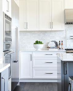 white shaker panel cabinets + dark grey island + marble backsplash