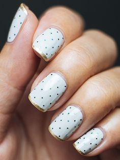 Glittery blue polka dots paired with a shiny gold stripe really make this white mani pop.