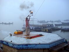 Priest offering prayers to the elements of nature on the banks of the river Ganges at dawn - Varanasi, Uttar Pradesh, India