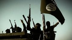 An image grab taken from a video released on March 17, 2014 by the Islamic State of Iraq and the Levant's al-Furqan Media allegedly shows ISIL fighters raising their weapons with the Jihadist flag at an undisclosed location