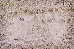 Handprints in the sand with wedding bands for a destination wedding