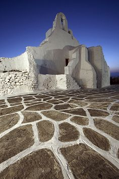 Church of Panagia Paraportiani is an iconic 15th Century church located in the heart of Mykonos, Greece. Photographed at twilight, the painted paving stone found throughout the island lead the eye into the frame and up to the church.