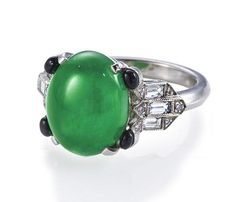 An art deco jadeite jade and diamond ring, circa 1925  centering an oval cabochon jadeite jade, measuring approximately 10.7 x 13.4 x 5.5mm., with round cabochon onyx detail, baguette and round brilliant-cut diamond shoulders and a beveled mount; mounted in platinum