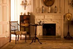 Thorne Miniature Room - Federal Period Piecrust Tripod Table with armchair. Note the elegant fireplace mantle.