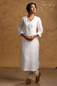 This formal long linen kurta in pure white has a semi button down front and a softly curved v-neck. Classic chic. Tellicherry is an ancient port town in Kera...