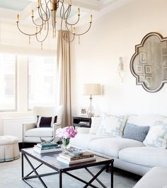 White furniture, black coffee table, hanging gold light, clear lamp, and mirror hanging above the couch
