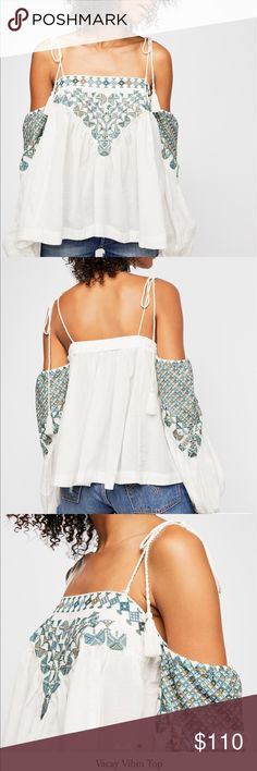 FP Vacay Vibin Top Lightweight top featuring colorful tribal-inspired embroidery detailing in an open shoulder silhouette.  • Elastic band at the back bust and arms • Adjustable shoulder ties • Semi-sheer  *55% Cotton *45% Rayon *Machine Wash Cold *Import Free People Tops