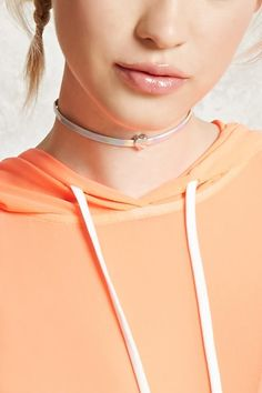 A faux leather choker featuring an iridescent sheen, a high-polish heart charm, and a lobster clasp closure.