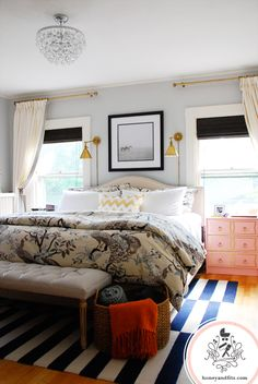Eclectic bedroom with pair of gold sconces above the bed. Stupid rug, floral duvet cover, black roman shades.