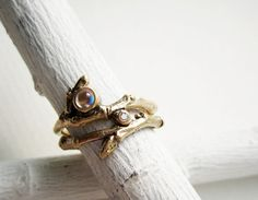Glimmering moonstone and sparkling diamond, set in a band of tag-like gold.