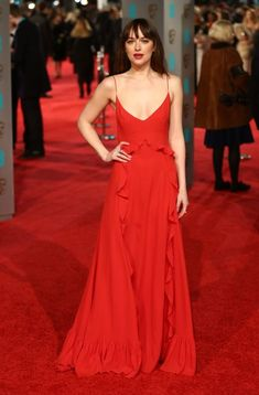 Dakota Johnson steps out in a red Dior gown. See all the best red carpet looks from the 2016 BAFTAS here: