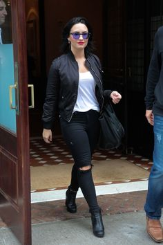Demi Lovato wearing  Topshop Ultimate MA1 Bomber Jacket, Prada Sport Black Leather Ankle Booties, Lionette NY Isla Earrings, Céline Boston Bag, Topshop Moto Washed Leigh Jeans, Ray-Ban Lightweight Clubmaster Sunglasses