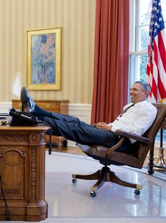 President Barack Obama in a laid back posture behind his Oval Office desk (February 5, 2013)