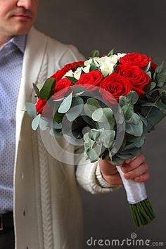 In the hands of a man beautiful bouquet of roses