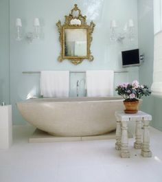 Modern tub, Sleek towel rod, Cool walls, mixed with Soft glass sconces, Antique French Mirror and flowers makes this elegant space inviting. Simply adore Vicente Wolf