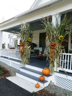 Fall idea for front porch ROCKS AROUND FOUNDATION... Love the cornstalks on post of porch.  Ive always put them in the yard....not this year