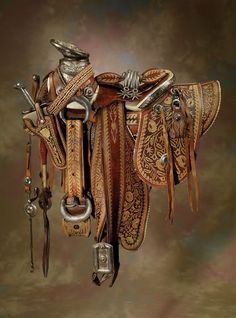 "Ornate Mexican Saddle with Headstall, Bit, Spurs, Chaps, Sword with Scabbard, Saddlebags, Belt & Holster: exposed rawhide covered tree with lavish floral and figural silver mountings, three-dimensional silver horn with raised Mexican Eagle, sterling Eagles on both swells, lavishly embroidered with piteado (cactus fiber), silver inlaid sword with inscription that reads: ""Si ami dueno ofendiereis de mi lavenganza esperes"" (If you offend my honor my revenge awaits you)."