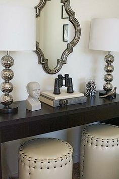 gorgeous entry design! dark wood console table, ivory leather round stools with nailhead trim tucked underneath, metal ball lamps and miror. {Caitlin Creer Interiors}