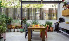 Cadeiras de ferro coloridas (Desmobilia) cercam a mesa de madeira maciça, protegida por uma cobertura de vidro temperado (Alves Silva Engenharia). No fundo, a mini-horta fornece temperos para os grelhados.