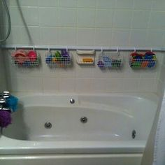 Add an extra shower rod and hang wire baskets with shower curtain rings to the rod. great way to keep toys out of the tub :)