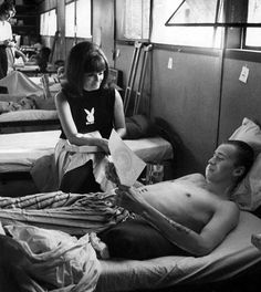 "Bien Hoa, South Vietnam, January, 1966: Playboy magazine playmate Jo Collins talks with a servicemember in the Army hospital at Bien Hoa. Collins, Playboy's 1965 Playmate of the Year, said in an interview that women should send the troops letters and photos. ""Some of the boys are not getting mail from home and they feel kind of sad,"" she said."