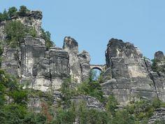 """...thront in 305 Metern Höhe die Basteiaussicht (links) über dem Elbtal, die bekannte Basteibrücke verbindet die einzelnen Felsen der """"Mardertelle"""" genannten Schlucht zwischen der Bastei und der Felsenburg Neurathen."""
