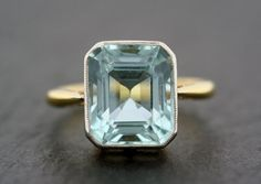 A beautiful Art Deco aquamarine ring. A single octagonal aquamarine in a simple millegrain-edge platinum set 18ct gold ring. The setting has some classic chenier tube detail and is particularly Art Deco in style. A fabulous statement ring!  Gemstones: - The main stone is an octagonal step-cut aquamarine of a sea-green/blue colour. It measures approximately 12.3mm x 10.6mm.  Hallmarks: - There is an 18CT stamp inside the ring. There is also a makers mark - F.T. The white metal on top of the…
