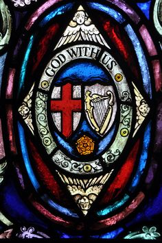 "stained glass window/ Depicting the cross, the crown of gloryand ""God with us"" being the name of Christ, Emmanuel."