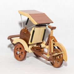 Wooden Pedicab Hand Crafted. This piece of model wood art required a lot of workmanship since it was hand-crafted from many different pieces of wood to make a beautiful model.