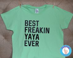 "This fun tee is exactly what your yaya needs. Our made-to-order shirt features black and black glittery lettering on a light green t-shirt. The text reads Best Freakin Yaya Ever. The words Yaya is in black glittery lettering, while the other words are in regular/flat black lettering.  All of our products are made to order. If you'd like a different color combination (see image showing our options), include that info in the ""notes to seller"" section when you are making your purchase…"