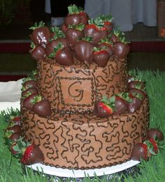 Chocolate covered strawberries on top and some scattered on base and middle layer.