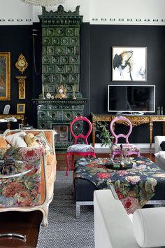Mustassa salissa värit ja kuviot hehkuvat tummaa taustaa vasten. Kivikantiset, kullanväriset sivupöydät ovat Portugalista. Rokokootyylisen sohvan parina on italialaisia designkalusteita. Television yläpuolella on nizzalaisen Daniel Agostinin maalaus.