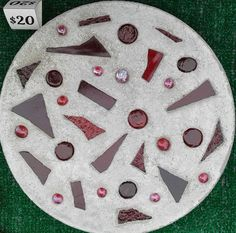 """This 12"""" solid concrete circle garden accent has red glass beads and shards of tumbled red glass embedded into the concrete. It weighs about 12lbs and was sprayed with acrylic UV protectant spray and brushed with low gloss acrylic concrete sealer. 
