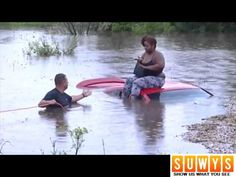 Woman on the phone when rescue comes for her on top of her sinking car