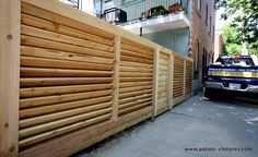 Robust horizontal louvered fence. The posts, the top and bottom horizontal rails are made of 6x6 and the louvers are made with thick decking floorboards.