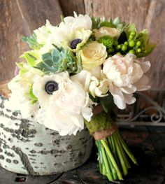This classic and timeless Bridal Bouquet contains a perfect combination of Cream, Green, Blush Pink, and White color pallet. White Peonies, Antique Anenimonies, Mondile Roses, Succulents, Green Hypericum Berries, Green Cymbidium Orchids, Fresh Lavender and Rustic Artichokes were used to style this beauty. Berlap fabric was wrapped around the handle and the accented with a moss embellishment. Simply stunning...  www.BlushingBloomsAtlanta.com