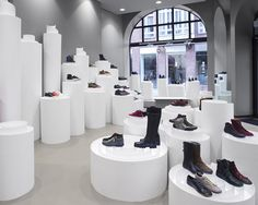 nendo's rolled paper-like pillars present shoes at camper stockholm