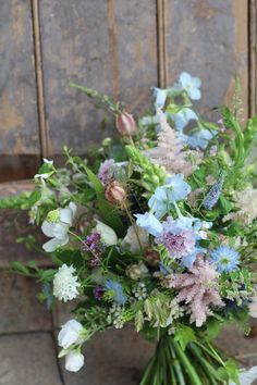 wild and natural hand tied bouquet created from a mixture of British flowers in pale pinks, pale blues, whites, lilacs and greens