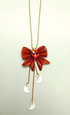 Sailor Moon Inspired Bow Necklace with Hanging Mother of Pearl Moon Charms. $29.50, via Etsy.