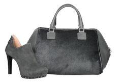 Zapato abotinado de color gris con tacón fino y decorado con tachuelas junto a bolso de pelo