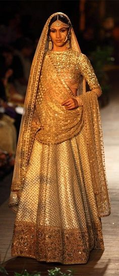 A beautiful gold colored bridal lehenga displayed at one of the Delhi Couture Week events. Source: Appily Ever