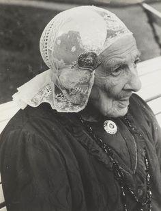 Oude vrouw in Friese streekdracht. 1900-1925 Oude vrouw in Friese streekdracht. Ze draagt een oorijzer met daarover een kanten muts. #Friesland