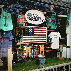 Our July 2015 display window features new art from local Raleigh artist Alan Swartwood of Rough Cut Flags. He creates the American Flag i the center from recycled wood pallets. New hand painted birdhouses from local artist Mary Jo Stephenson. The white t-shirt from local designer Old North Rags Clothing. This shirt is made from NC/SC cotton, sewn, designed and printed in the Triangle!