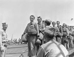 LT Mary Jane Hinckley of Millville, NJ and nurses of the 95th Evacuation Hospital being checked off the loading roster as they load on a ship that will take them to their unit on the invasion front on the southern coast of France.